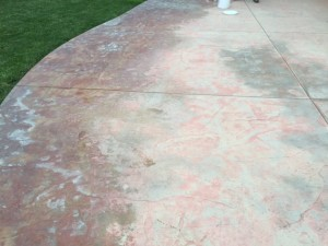 A worn, discolored, stamped patio - Before